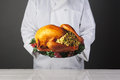 Chef holding thanksgiving turkey on platter closeup of a a with a with all the trimmings horizontal format over a light to dark Royalty Free Stock Photos