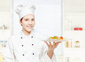 Chef holding vegetarian meal in kitchen Stock Photo