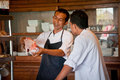 Chef instructing trainee in restaurant kitchen canggu bali indonesia how to cut a fish Royalty Free Stock Photography