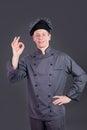 Chef kok showing ok sign op grijze achtergrond Stock Foto's