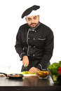 Chef male cutting sald in black uniform salad isolated on white background Stock Photography