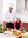 Chef master and junior pupil kid girl at cooking school with food on countertop Royalty Free Stock Photos