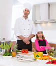 Chef master and junior pupil kid girl at cooking school with food on countertop Royalty Free Stock Image