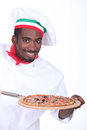 Chef with pizza on a wooden peel Stock Photography