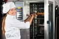 Chef placing pizza in oven portrait of happy female at commercial kitchen Stock Image