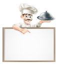 Chef pointing at sign a cartoon character holding a silver platter or cloche Royalty Free Stock Photography