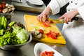 Chef preparing salad cutting tomato on yellow cutting board Stock Image
