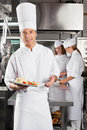 Chef presenting dish in commercial kitchen portrait of young with colleagues standing background at Stock Photography