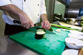 Chef in a professional kitchen slicing zucchini Stock Images