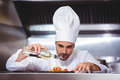 Chef putting finishing touch on salad in commercial kitchen Royalty Free Stock Photo