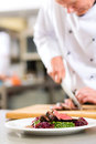 Chef in restaurant kitchen preparing food hotel or cooking he is cutting meat or steak for a dish on plate Stock Image