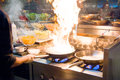 Chef in restaurant kitchen at stove with pan, doing flambe on food. low ligth selective focus. Royalty Free Stock Photo