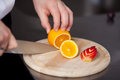 Chef s hand cutting orange for garnishing closeup of in commercial kitchen Royalty Free Stock Image
