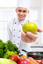 Chef showing fresh green apple to camera in the kitchen Royalty Free Stock Photos