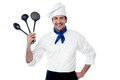 Chef showing kitchen essentials handsome male holding utensils Stock Photos