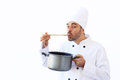 Chef taste soup in white toque holding a pot and Stock Photos