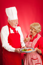Chef teaching sweet elderly grandma how to cook authentic italian spaghetti marinara red background copy space Stock Images