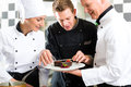 Chef team in restaurant kitchen with dessert Royalty Free Stock Photography