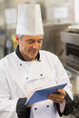 Chef touching his digital tablet in the kitchen Royalty Free Stock Photography