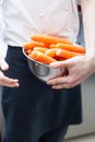 Chef in uniform preparing fresh carrot batons Royalty Free Stock Photo