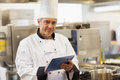Chef using his digital tablet and looking at camera in the kitchen Royalty Free Stock Images
