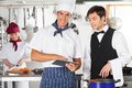 Chef with waiter using digital tablet portrait of male in commercial kitchen Royalty Free Stock Photography