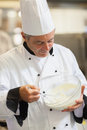 Chef whisking cream in the kitchen Stock Images