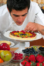 Chef young handsome making fruit tarts Royalty Free Stock Photography