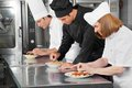 Chefs garnishing dishes on counter three commercial kitchen Royalty Free Stock Images