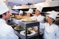 Chefs handing dinner plates through order station Royalty Free Stock Photo
