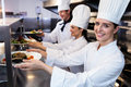 chefs handing dinner plates through order station Royalty Free Stock Photo
