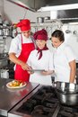 Chefs looking for recipe on digital tablet three in commercial kitchen Royalty Free Stock Image