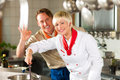 Chefs in a restaurant or hotel kitchen cooking two teamwork men and women delicious food Royalty Free Stock Photography
