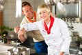Chefs in a restaurant or hotel kitchen cooking two teamwork men and women delicious food Stock Images