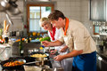 Chefs in a restaurant or hotel kitchen cooking two teamwork men and women delicious food Royalty Free Stock Image