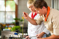 Chefs in a restaurant or hotel kitchen cooking two teamwork men and women delicious food Stock Image