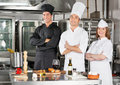 Chefs standing with arms crossed portrait of confident by kitchen counter Royalty Free Stock Images