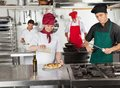 Chefs working in restaurant kitchen female chef pouring oil dish with colleagues Royalty Free Stock Images