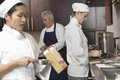 Chefs working together in commercial kitchen three busy Stock Photography