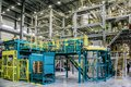 Chemical factory. Thermoplastic production line and packing machinery in large area of industrial hall
