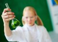 Chemical liquid image of flasks with green held by schoolgirl Stock Photography
