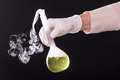 Chemical reaction in volumetric flask glass kept in the hands of Royalty Free Stock Photo