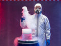 Chemist experimenting with vapors on blue barrel person in a protective suit and gas mask steaming substances over a plastic waste Stock Photos