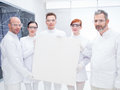 Chemist laboratory team close up of five scientists in a chemistry lab holding in hands an empty banner and confident looking in Stock Photo