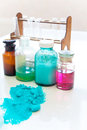 Chemistry bottles containing various substances of different colors standing on laboratory table seen over a pile of blue powder