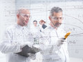 Chemistry lab data analysis general view of two scientists scaning and analyzig formulas on a transparent board with two students Royalty Free Stock Image