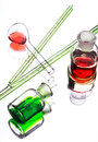 Chemistry laboratory glassware with colour liquids on white back in them background Stock Photography
