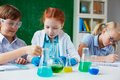At chemistry lesson three children working with chemical liquids Royalty Free Stock Images