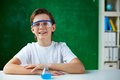 Chemistry lover portrait of smiling schoolboy sitting at workplace with chemical liquid in front Stock Images