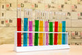 Chemistry test tubes with different colored liquids standing glass various coloured in front of periodic table Stock Photography